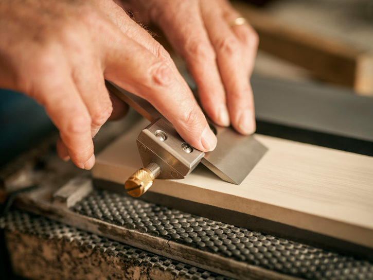Plane blade in a honing guide ready to sharpen on a waterstone