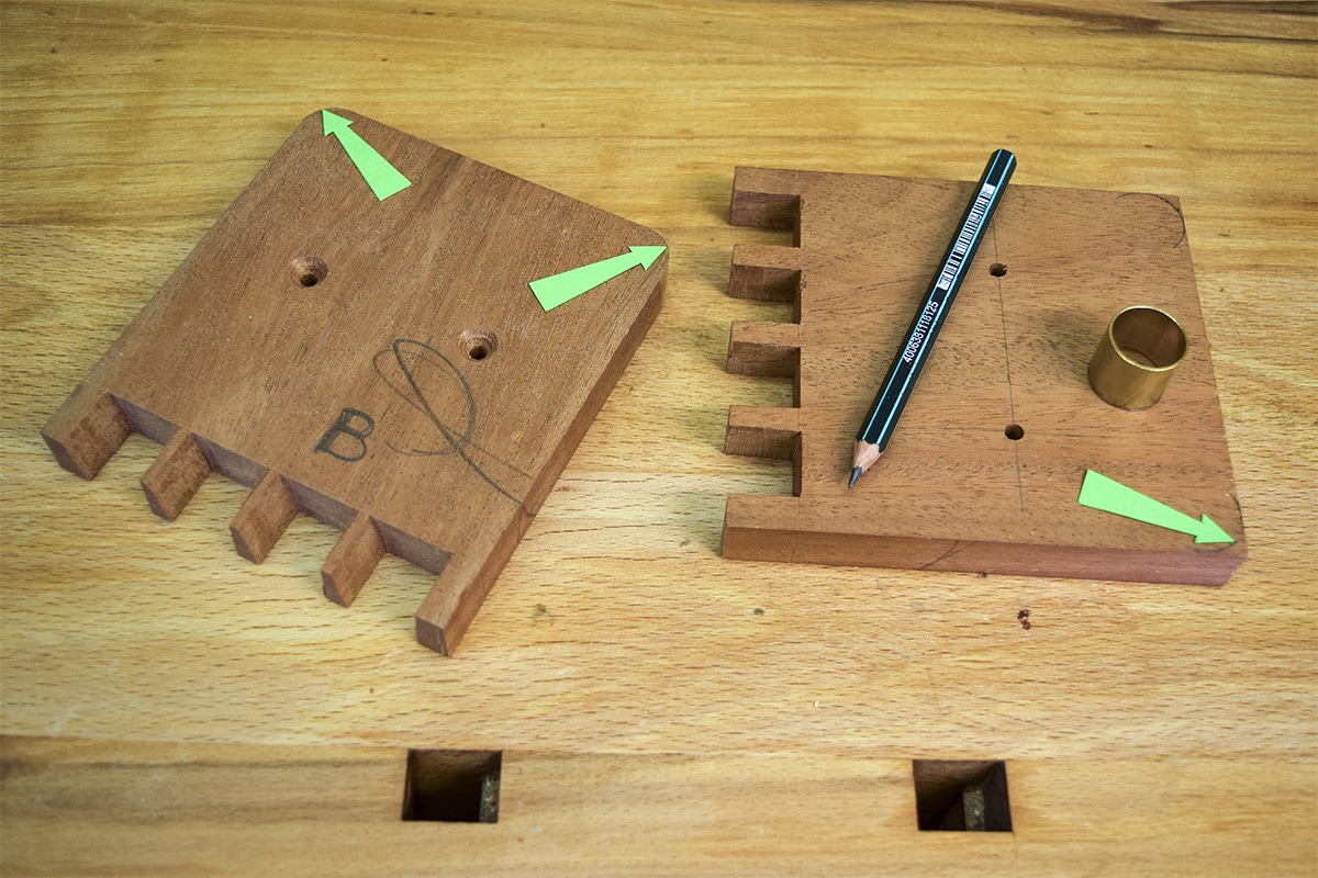 2 sections of mahogany with drilled holes in the centre of each, with a pencil and curved tool for rounding corner edges.