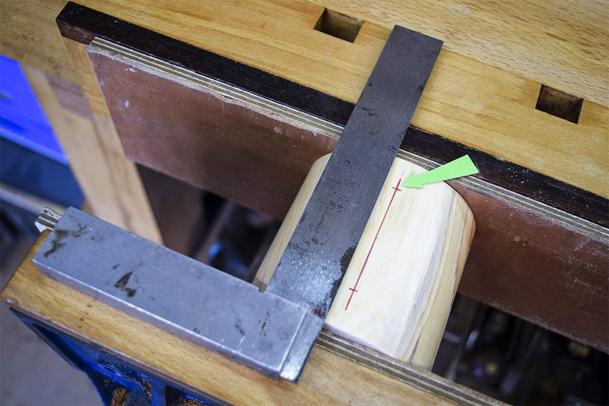 Section of Yew clamped into workbench with marked out lines for screw holes.