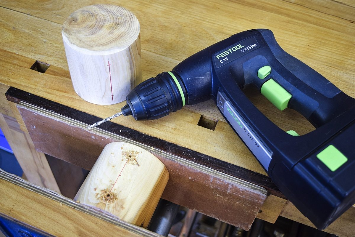 Turned Yew rounds with hold for screws drill out with drill on workbench.