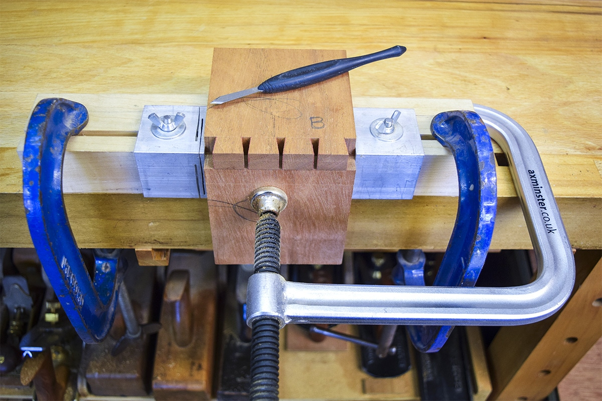 Marked out pin boards on second sections of mahogany, clamped to the workbench.