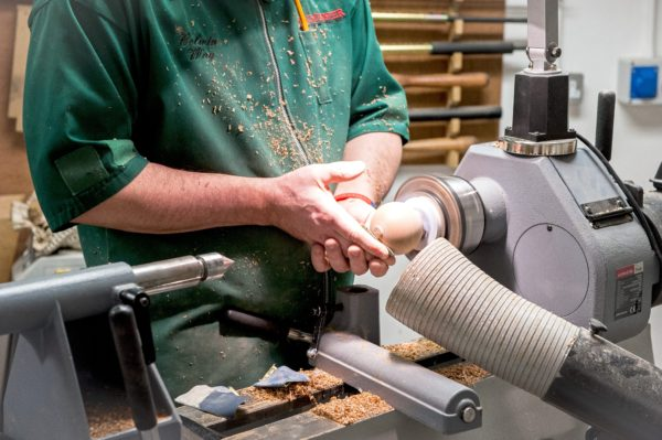 Sanding the top section of the pepper mill on a lathe.