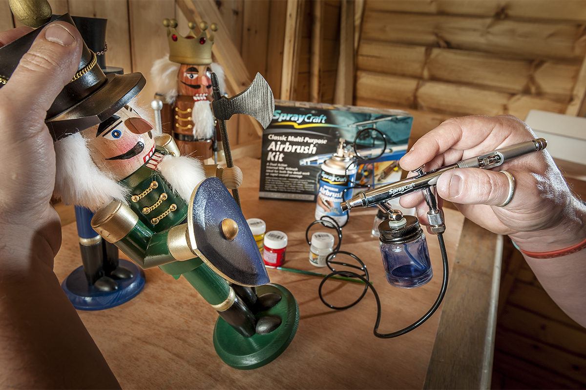 Airbrushing with canned propellant a nutcracker toy