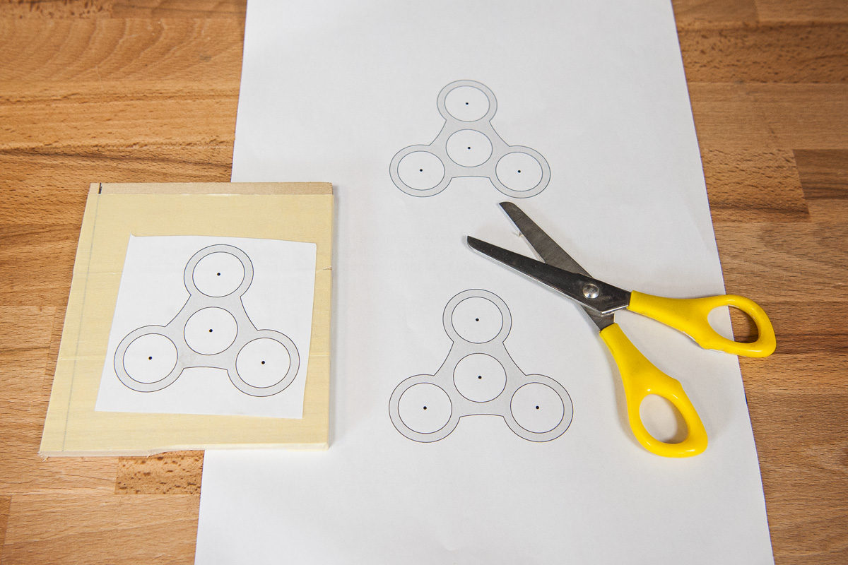 Fidget spinner pattern roughly cut out and glued to timber