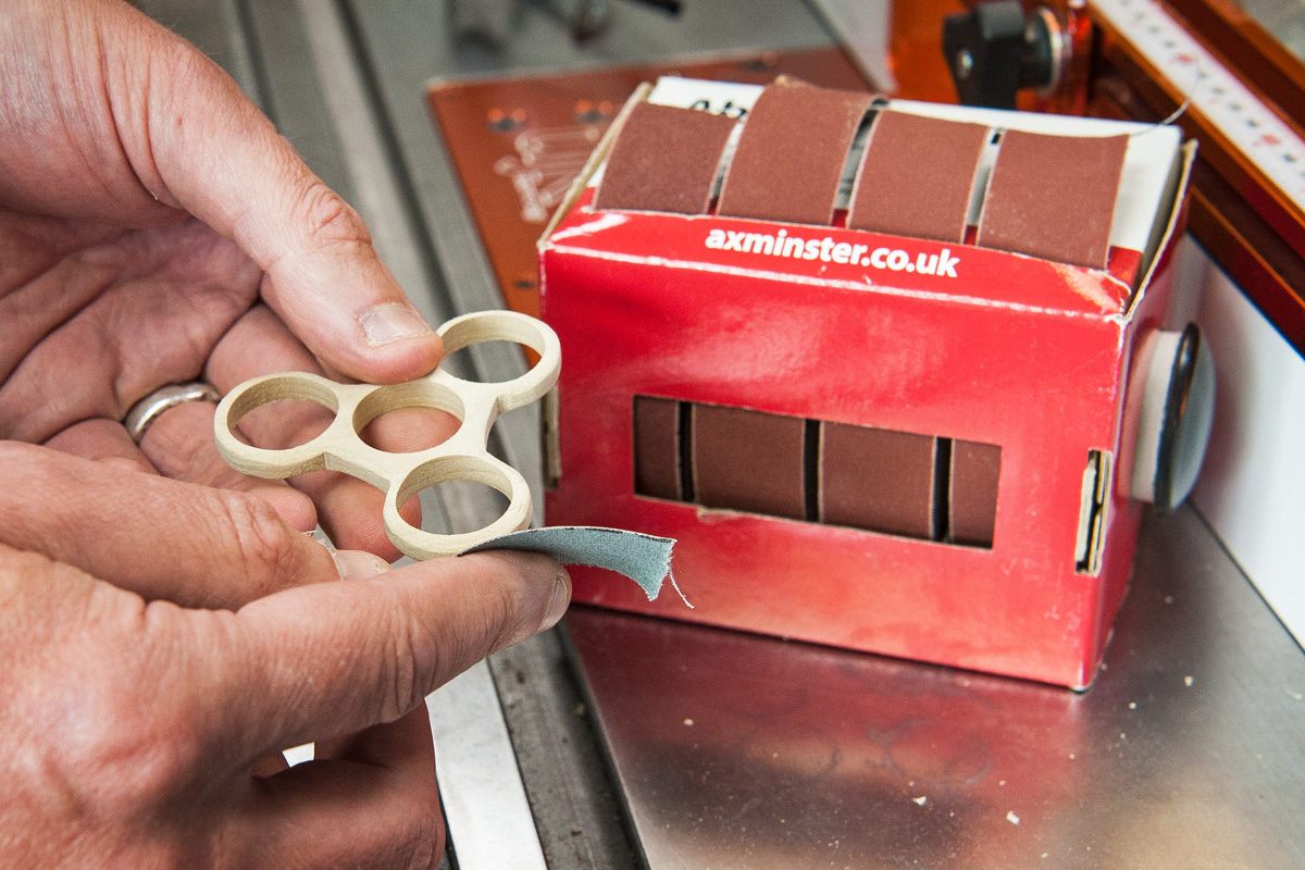 Fidget spinner being smoothed with abrasive strip