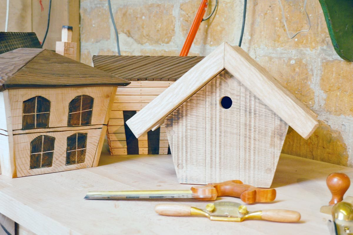 Hand tools in front of three wooden birdboxes