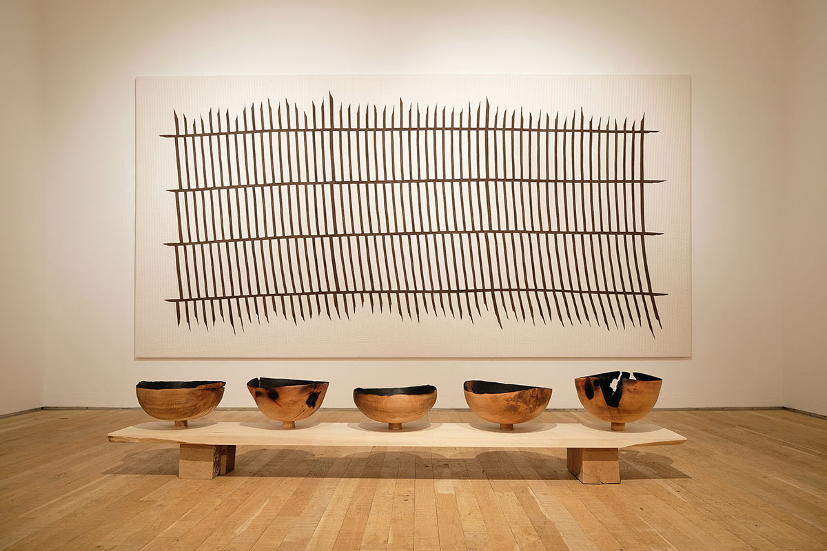 exhibition shot of wood turned and sculptured bowls and tapestry