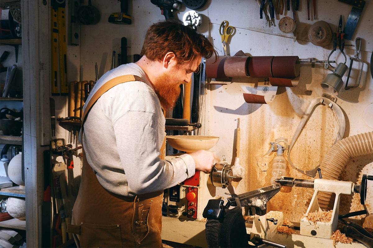sculptor max woodturning on his lathe in the workshop